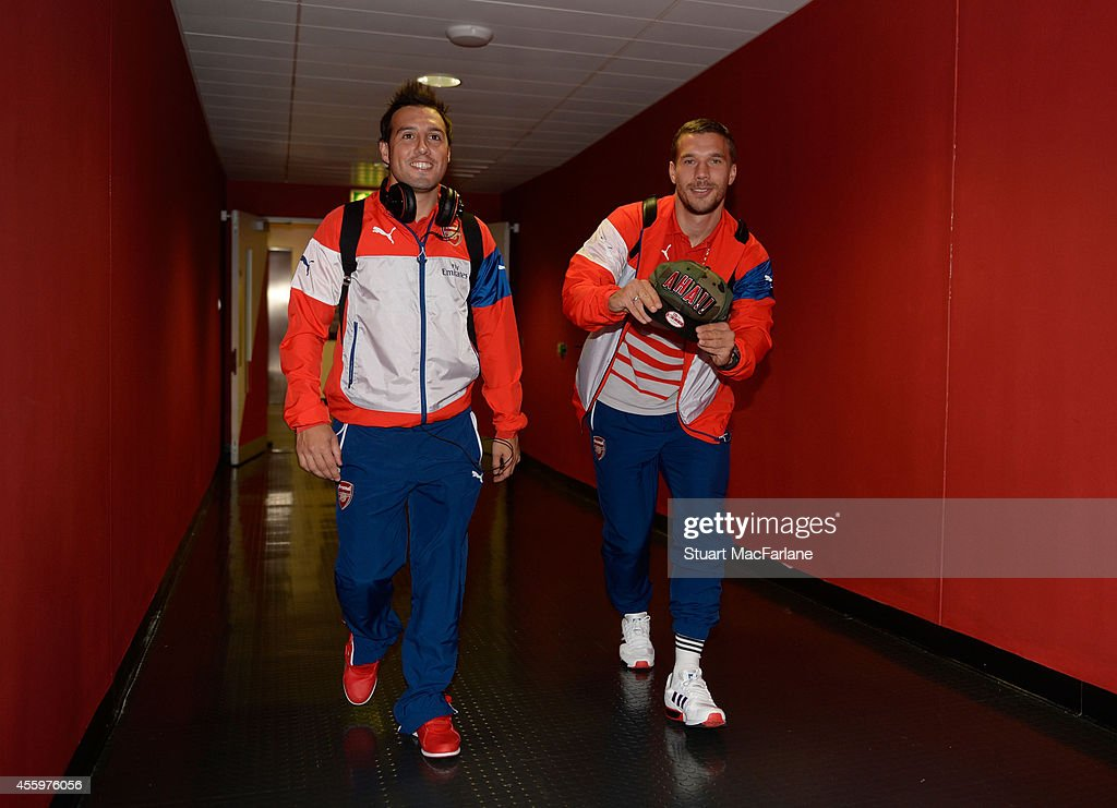 Arsenal's (L-R) Santi Cazorla and Lukas Podolski arrive at the players entrance before the Capital One Cup Third Round match between Arsenal and Southampton at Emirates Stadium on September 23, 2014 in London, England.