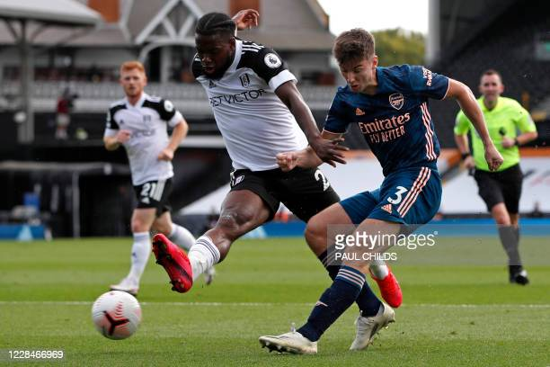 Arsenal's Scottish defender Kieran Tierney crosses as Fulham's English midfielder Josh Onomah defends during the English Premier League football...