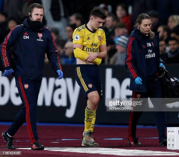Arsenal's Scottish defender Kieran Tierney holds his arm as he walks off the pitch injured during the English Premier League football match between...