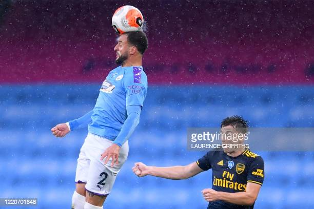 Arsenal's Scottish defender Kieran Tierney reacts as Manchester City's English defender Kyle Walker headers the ball during the English Premier...