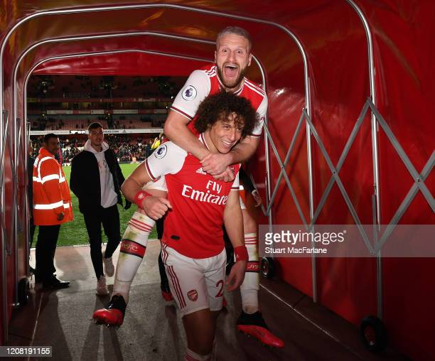 Arsenal's Shkodran Muatafi and David celebrate after the Premier League match between Arsenal FC and Everton FC at Emirates Stadium on February 23,...