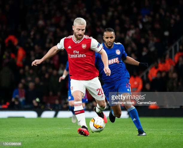 Arsenal's Shkodran Mustafi shields the ball from Olympiakos' Youssef El Arabi during the UEFA Europa League round of 32 second leg match between...