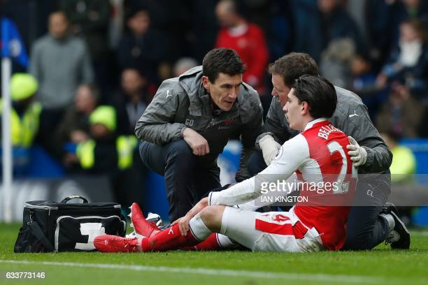 Arsenal's Spanish defender Hector Bellerin receives attention on the pitch after clashing in the air with Chelsea's Spanish defender Marcos Alonso...