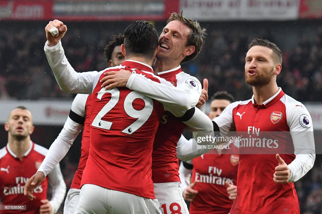 Arsenal's Spanish defender Nacho Monreal (C) celebrates after scoring with Arsenal's Swiss midfielder Granit Xhaka during the English Premier League football match between Arsenal and Crystal Palace at the Emirates Stadium in London on January 20, 2018. / AFP PHOTO / Ben STANSALL / RESTRICTED TO EDITORIAL USE. No use with unauthorized audio, video, data, fixture lists, club/league logos or 'live' services. Online in-match use limited to 75 images, no video emulation. No use in betting, games or single club/league/player publications. /