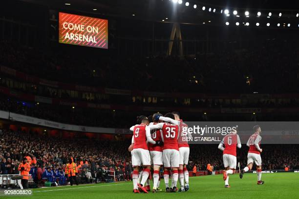 Arsenal's Spanish defender Nacho Monreal celebrates scoring the team's first goal with teammates during the League Cup semifinal football match...