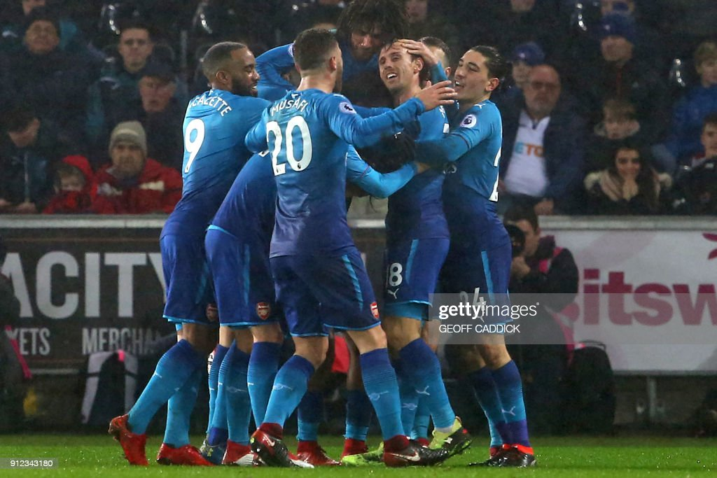 Arsenal's Spanish defender Nacho Monreal (2nd R) celebrates with teammates after scoring the opening goal of the English Premier League football match between Swansea City and Arsenal at The Liberty Stadium in Swansea, south Wales on January 30, 2018. / AFP PHOTO / Geoff CADDICK / RESTRICTED TO EDITORIAL USE. No use with unauthorized audio, video, data, fixture lists, club/league logos or 'live' services. Online in-match use limited to 75 images, no video emulation. No use in betting, games or single club/league/player publications. /