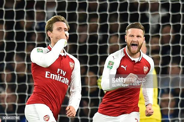 Arsenal's Spanish defender Nacho Monreal celebtrates scoring the team's first goal with Arsenal's German defender Shkodran Mustafi during the League...