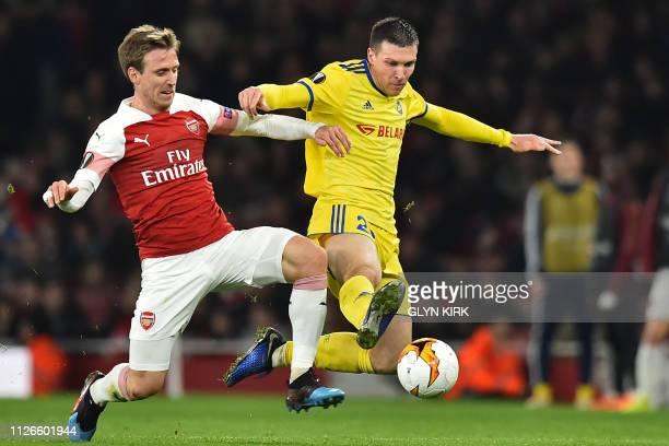 Arsenal's Spanish defender Nacho Monreal vies with BATE Borisov's Serbian striker Nemanja Milic during the UEFA Europa League round of 32 2nd leg...