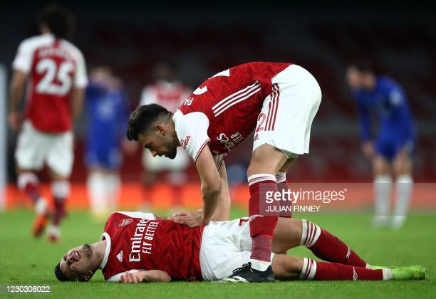 Arsenal's Spanish defender Pablo Mari speaks to injured Arsenal's Brazilian striker Gabriel Martinelli during the English Premier League football...