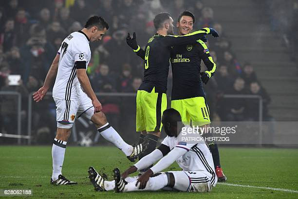Arsenal's Spanish forward Lucas Perez celebrates after scoring a goal with his teammate Arsenal's German midfielder Mesut Ozil next to Basel's...