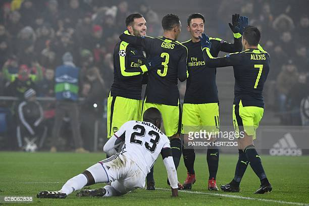 Arsenal's Spanish forward Lucas Perez celebrates after scoring a goal with his teammates Arsenal's English defender Kieran Gibbs Arsenal's German...
