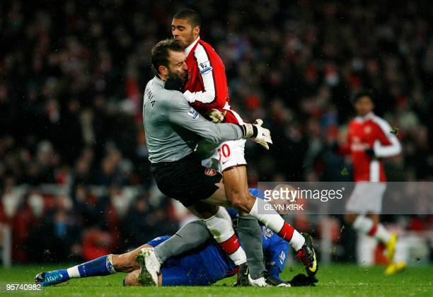 Arsenal's Spanish goalkeeper Manuel Almunia collides with team-mate French defender Armand Traore and Everton's English striker James Vaughan during...