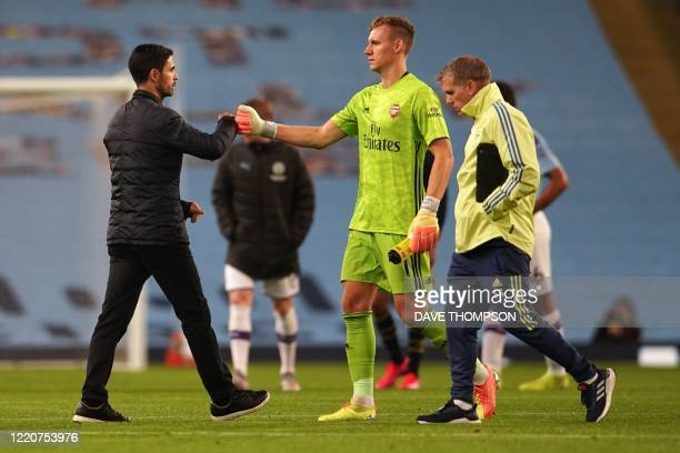 Arsenal's Spanish head coach Mikel Arteta bumps fists with Arsenal's German goalkeeper Bernd Leno after the final whistle during the English Premier...