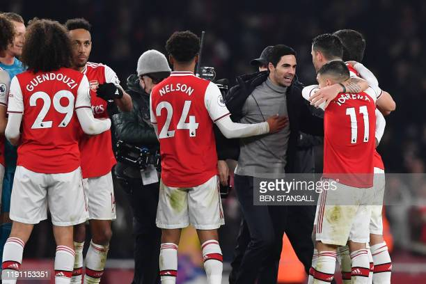 Arsenal's Spanish head coach Mikel Arteta celebrates with his players on the pitch after the English Premier League football match between Arsenal...
