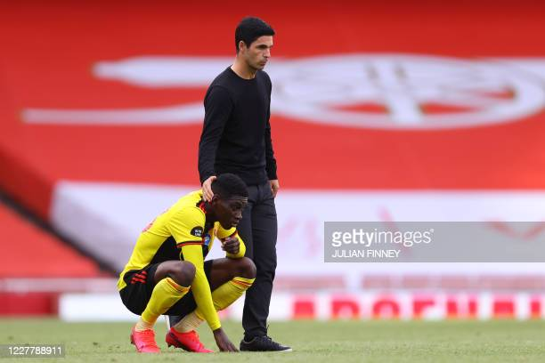 Arsenal's Spanish head coach Mikel Arteta commiserates with Watford's Senegalese midfielder Ismaila Sarr after losing the English Premier League...