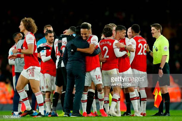 Arsenal's Spanish head coach Mikel Arteta embraces Arsenal's Gabonese striker PierreEmerick Aubameyang as Asrenal's players celebrate on the pitch...