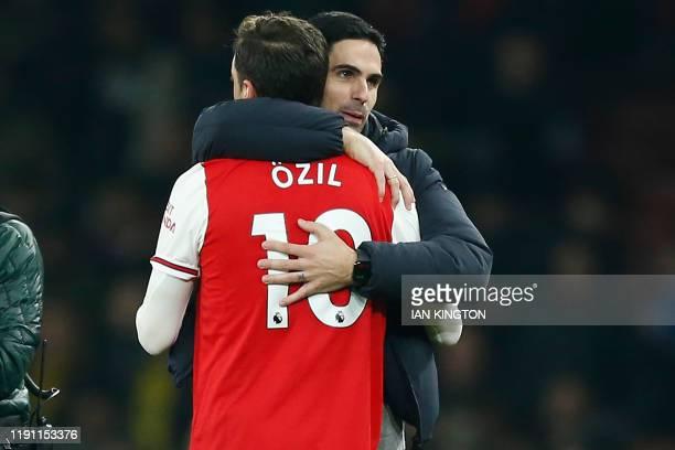 Arsenal's Spanish head coach Mikel Arteta embraces Arsenal's German midfielder Mesut Ozil on the pitch after the English Premier League football...