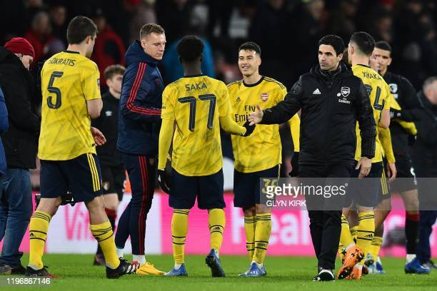 Arsenal's Spanish head coach Mikel Arteta shakes hands with his players on the pitch after the English FA Cup fourth round football match between...