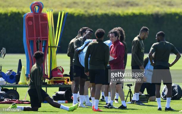Arsenal's Spanish head coach Unai Emery talks with his players during a training session at Arsenal's London Colney training centre in St. Albans on...