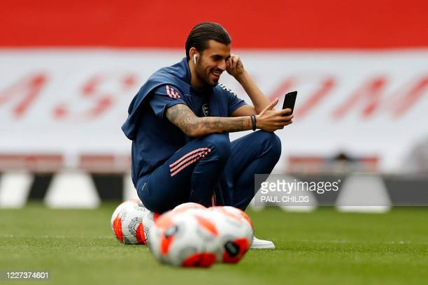 Arsenal's Spanish midfielder Dani Ceballos smiles as he checks his phone on the pitch ahead of the English Premier League football match between...