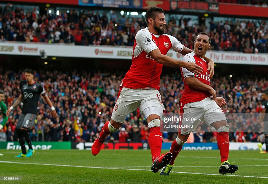 Arsenal's Spanish midfielder Santi Cazorla (R) celebrates with Arsenal's French striker Olivier Giroud after scoring the winning goal from the penalty spot during the English Premier League football match between Arsenal and Southampton at the Emirates Stadium in London on September 10, 2016. Arsenal won the game 2-1. / AFP / Adrian DENNIS / RESTRICTED TO EDITORIAL USE. No use with unauthorized audio, video, data, fixture lists, club/league logos or 'live' services. Online in-match use limited to 75 images, no video emulation. No use in betting, games or single club/league/player publications. /
