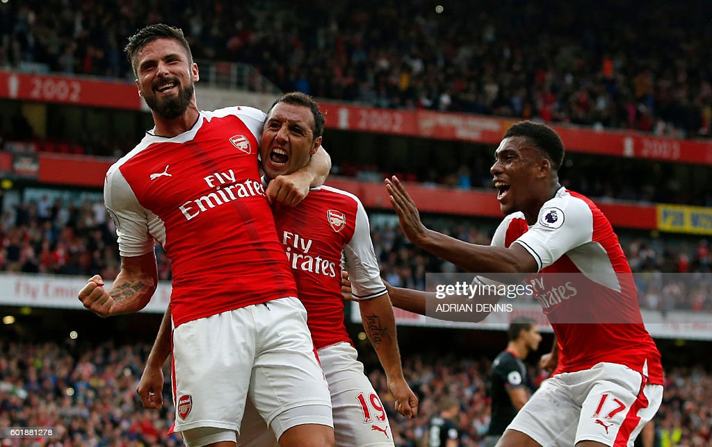 Arsenal's Spanish midfielder Santi Cazorla (C) celebrates with Arsenal's French striker Olivier Giroud and Arsenal's Nigerian striker Alex Iwobi (R) after scoring the winning goal from the penalty spot during the English Premier League football match between Arsenal and Southampton at the Emirates Stadium in London on September 10, 2016. Arsenal won the game 2-1. / AFP / Adrian DENNIS / RESTRICTED TO EDITORIAL USE. No use with unauthorized audio, video, data, fixture lists, club/league logos or 'live' services. Online in-match use limited to 75 images, no video emulation. No use in betting, games or single club/league/player publications. /