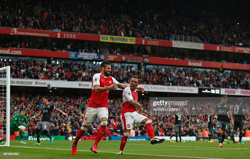 Arsenal's Spanish midfielder Santi Cazorla (centre right) celebrates with Arsenal's French striker Olivier Giroud after scoring the winning goal from the penalty spot during the English Premier League football match between Arsenal and Southampton at the Emirates Stadium in London on September 10, 2016. Arsenal won the game 2-1. / AFP / Adrian DENNIS / RESTRICTED TO EDITORIAL USE. No use with unauthorized audio, video, data, fixture lists, club/league logos or 'live' services. Online in-match use limited to 75 images, no video emulation. No use in betting, games or single club/league/player publications. /
