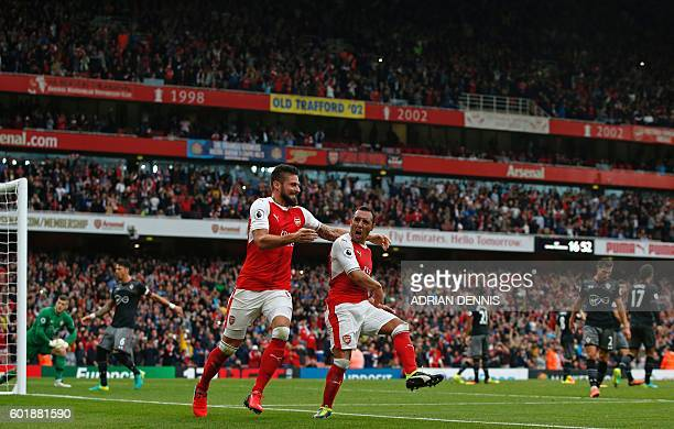 Arsenal's Spanish midfielder Santi Cazorla celebrates with Arsenal's French striker Olivier Giroud after scoring the winning goal from the penalty...