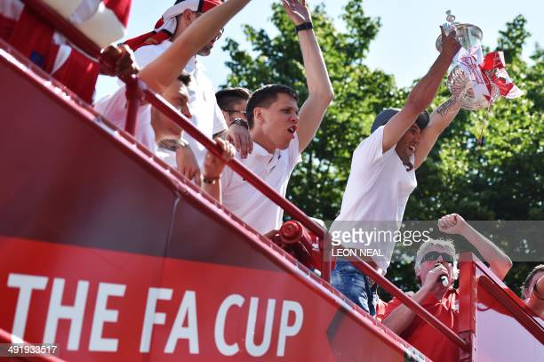 Arsenal's Spanish midfielder Santi Cazorla holds up the FA Cup their victory parade in London on May 18 following their win in the English FA Cup...