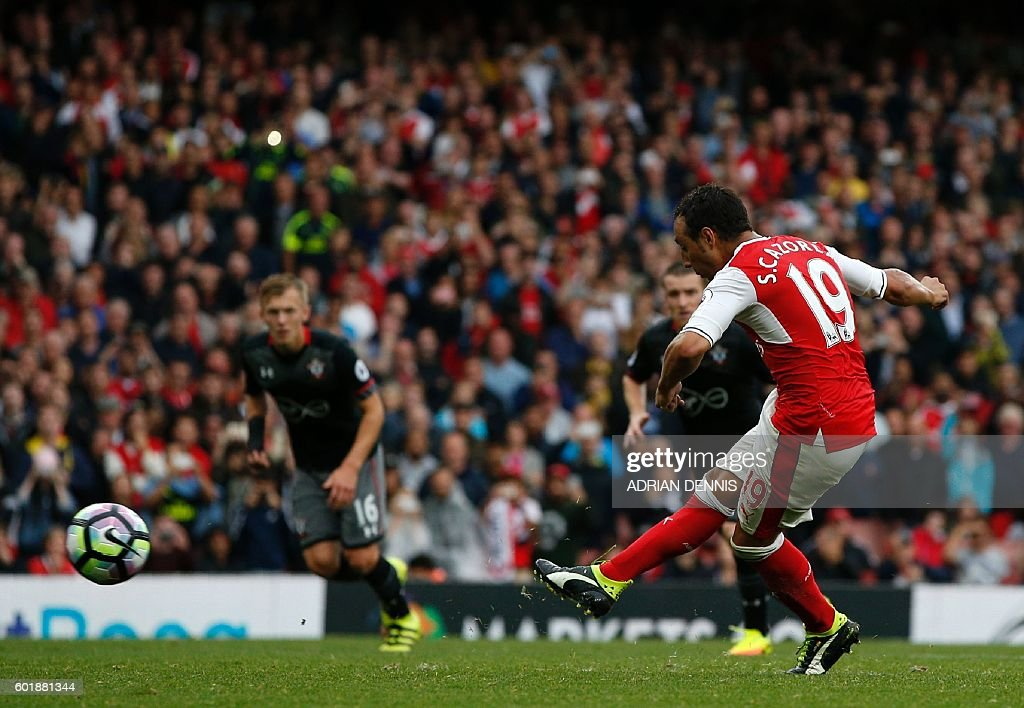Arsenal's Spanish midfielder Santi Cazorla (R) scores the winning goal from the penalty spot during the English Premier League football match between Arsenal and Southampton at the Emirates Stadium in London on September 10, 2016. Arsenal won the game 2-1. / AFP / Adrian DENNIS / RESTRICTED TO EDITORIAL USE. No use with unauthorized audio, video, data, fixture lists, club/league logos or 'live' services. Online in-match use limited to 75 images, no video emulation. No use in betting, games or single club/league/player publications. /