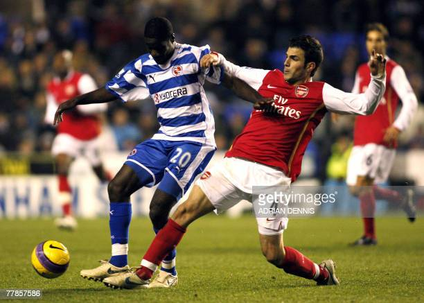 Arsenal's Spanish player Cesc Fabregas vies for the ball against Reading Emerse Fae the Premiership football match against Reading at the Madejski...