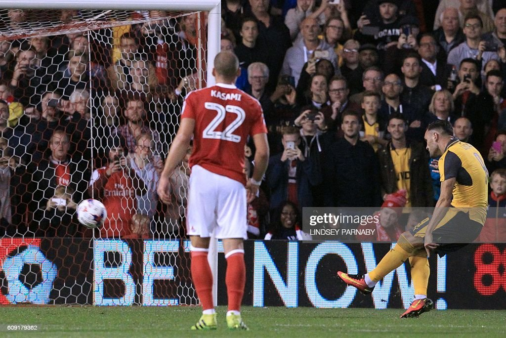 Arsenal's Spanish striker Lucas Perez (R) scores their second goal from the penalty spot during the English League Cup third round football match between Nottingham Forest and Arsenal at The City Ground in Nottingham, central England on September 20, 2016. / AFP / Lindsey PARNABY / RESTRICTED TO EDITORIAL USE. No use with unauthorized audio, video, data, fixture lists, club/league logos or 'live' services. Online in-match use limited to 75 images, no video emulation. No use in betting, games or single club/league/player publications. /