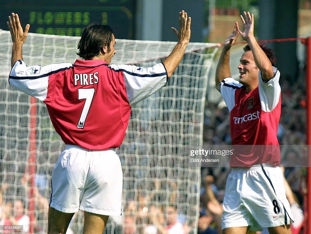 Arsenal's Swedish midfielder Frederik Ljungberg (R) and teammate French midfielder Robert Pires celebrate Ljungberg's goal that put his team one ahead of Leicester City during a premier league match at Highbury stadium in London , 25 August 2001.