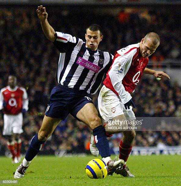 Arsenal's Swedish player Fredrik Ljunberg fights for the ball with West Bromwich Neil Clement during their Barclays Premiership football match at...