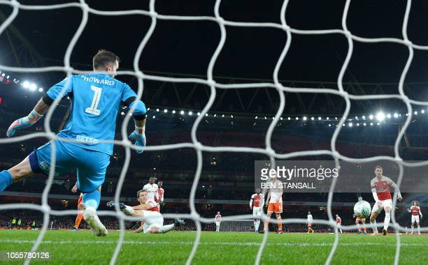 Arsenal's Swiss defender Stephan Lichtsteiner scores the opening goal past Blackpool's English goalkeeper Mark Howard during the English League Cup...