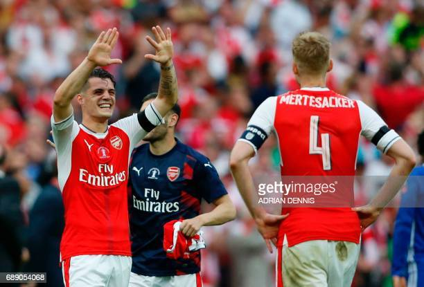 Arsenal's Swiss midfielder Granit Xhaka celebrates with Arsenal's German defender Per Mertesacker on the pitch after the English FA Cup final...