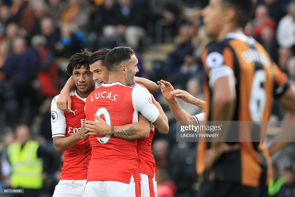 Arsenal's Swiss midfielder Granit Xhaka (C) celebrates with Arsenal's Egyptian midfielder Mohamed Elneny (L) after scoring their fourth goal during the English Premier League football match between Hull City and Arsenal at the KCOM Stadium in Kingston upon Hull, north east England on September 17, 2016. / AFP / Lindsey PARNABY / RESTRICTED TO EDITORIAL USE. No use with unauthorized audio, video, data, fixture lists, club/league logos or 'live' services. Online in-match use limited to 75 images, no video emulation. No use in betting, games or single club/league/player publications. /