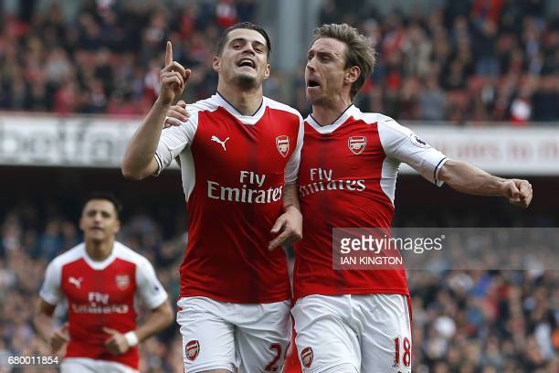 Arsenal's Swiss midfielder Granit Xhaka celebrates with Arsenal's Spanish defender Nacho Monreal after scoring the opening goal of the English...