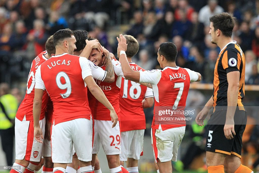 Arsenal's Swiss midfielder Granit Xhaka (C) celebrates with teammates after scoring their fourth goal during the English Premier League football match between Hull City and Arsenal at the KCOM Stadium in Kingston upon Hull, north east England on September 17, 2016. / AFP / Lindsey PARNABY / RESTRICTED TO EDITORIAL USE. No use with unauthorized audio, video, data, fixture lists, club/league logos or 'live' services. Online in-match use limited to 75 images, no video emulation. No use in betting, games or single club/league/player publications. /