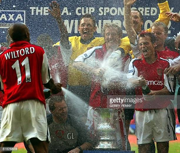Arsenal's Sylvain Wiltord sprays goal scorers Freddie Ljungberg and Ray Parlour with champagne after Arsenal beat Chelsea 20 in the FA Cup 04 May...