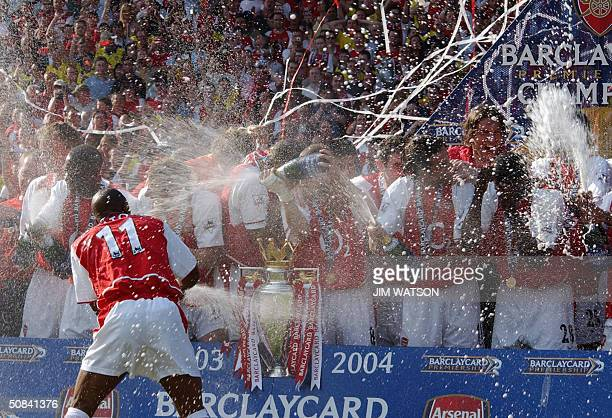 Arsenal's Sylvan Wiltord sprays his teammates with champaigne as they celebrate after winning the Premiership title and defeating Leicsester City 15...