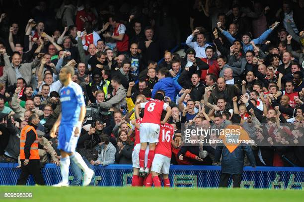 Arsenal's Theo Walcott celebrates with teammates in front of jubilant Arsenal fans after scoring their third goal of the game as Chelsea's Jose...
