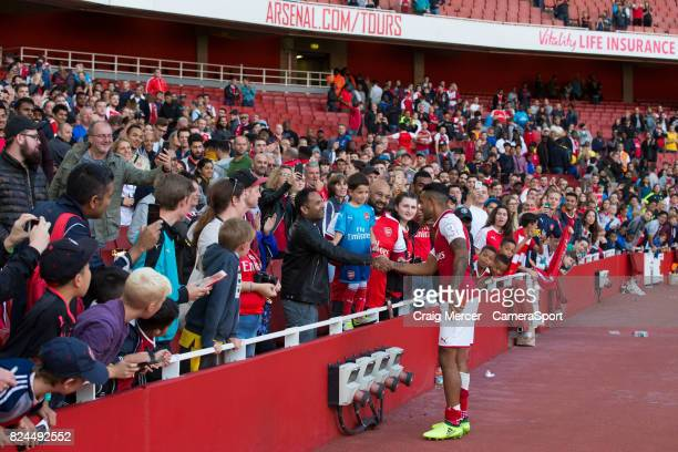 Arsenal's Theo Walcott gives his winners medal to a young fan after the Emirates Cup match between Arsenal and Sevilla FC at Emirates Stadium on July...