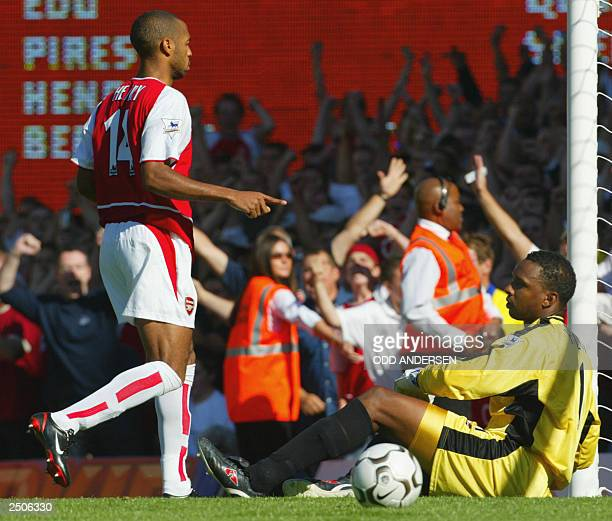 Arsenal's Thierry Henry celebrates scoring an equalizing penalty as Portsmouth's goalie Shaka Hislop sits on the pitch during their Premiership match...