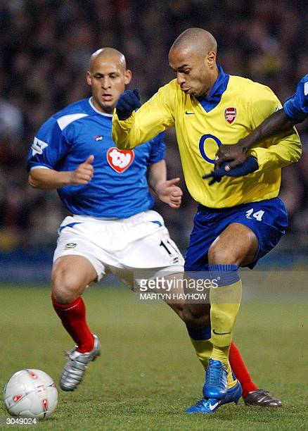 Arsenal's Thierry Henry gets the ball past Nigel Quashie of Portsmouth during their FA Cup Quarter Final football match in Portsmouth 06 March 2004...