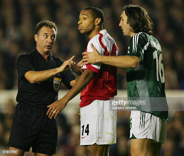Arsenal's Thierry Henry recieves a warning from referee Luis Medina Cantalejo as Panathinaikos' Sotirios Kirgiakos protests during their Champions...