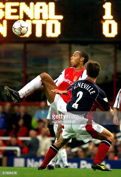 Arsenal's Thierry Henry tries to control the ball against Manchester United's Gary Neville in a Premiership match at Highbury in London 01 October...