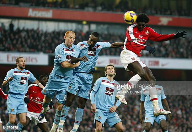 Arsenal's Togolese player Emmanuel Adebayor heads the ball at goal as he gets challenged from West Ham's Welsh player James Collins and Carlton Cole...