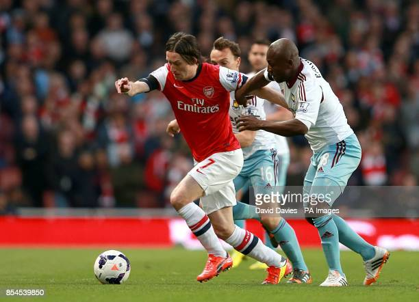 Arsenal's Tomas Rosicky gets away from and West Ham United's Pablo Armero as they battle for the ball
