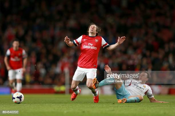 Arsenal's Tomas Rosicky goes down under a challenge from West Ham United's Mark Noble as they battle for the ball